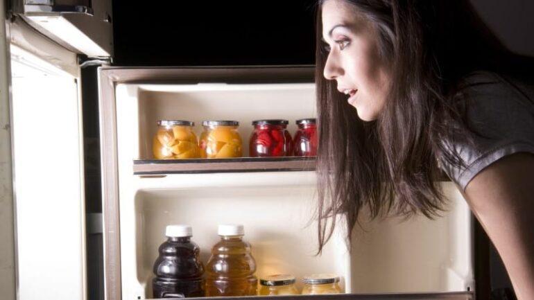 женщина открывает холодильник